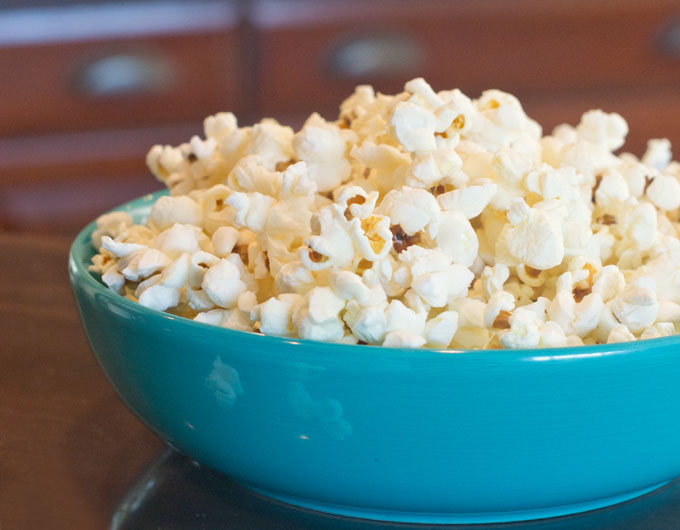 There was already oil used in the popping and so I find that you don't need to add melted butter. But need and want are different things. If you want it, add it. And sprinkle on some salt. Shake the pot again and then transfer the popcorn to a bowl.