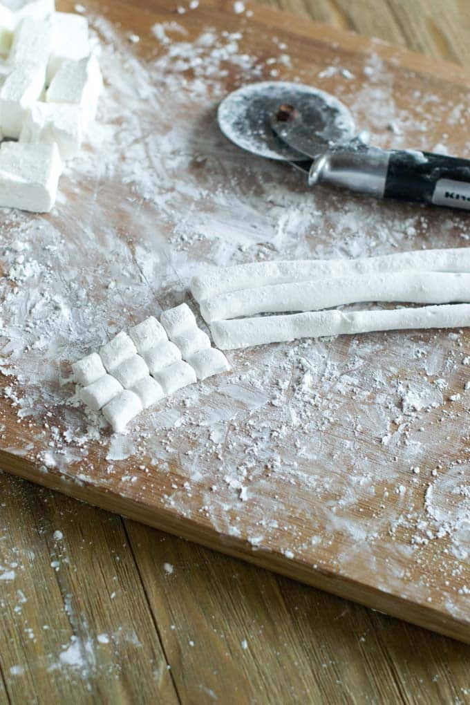 Making mini marshmallows by cutting on a wooden board.