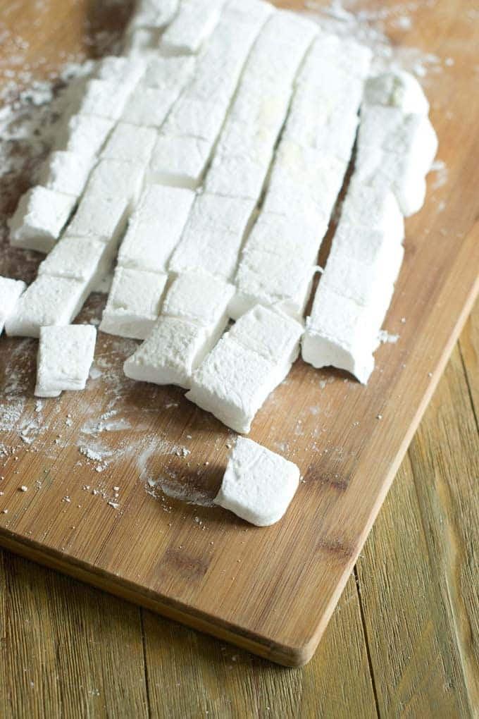 Cutting board full of large marshmallows.