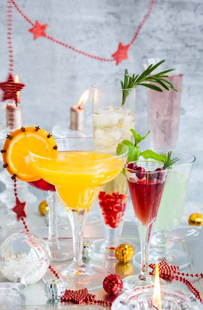 6 different champagne glasses filled with different drinks in all different colors sitting on a festive silver table with  red, yellow and silver baubles  a red beaded garland with stars in the back ground as well as two burning candles.