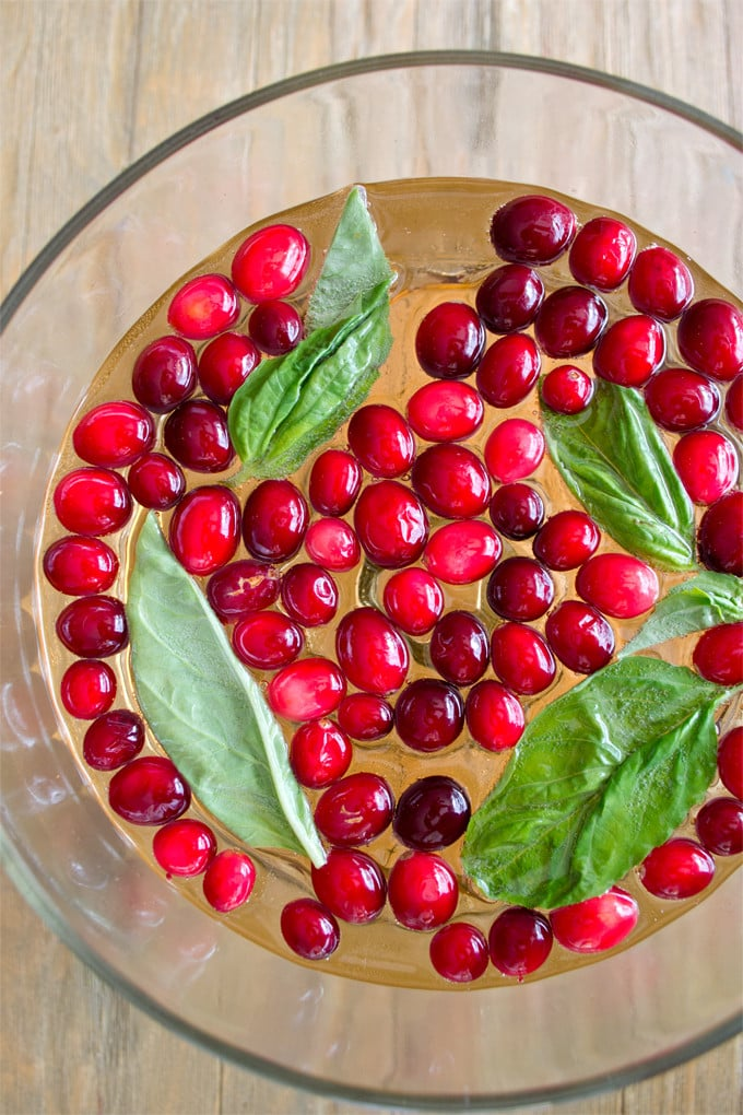 photo taken from directly above of a clear punch bowl filled with with whole cranberries floating in the punch with some whole basil leaves.