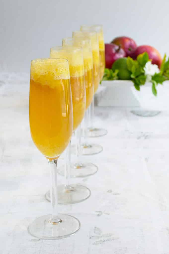 5 champagne flutes lined up in a row filled with mango bellinis on a white surface. In the background is a white bowl filled with green leaves and red mangos.