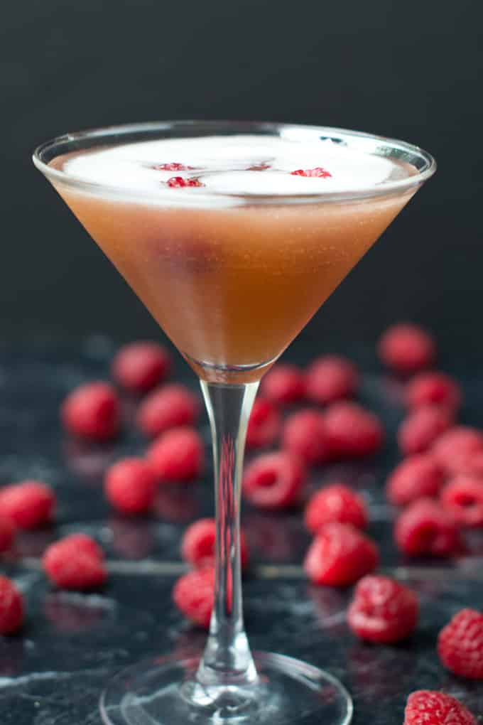 Martini glass filled with an amber looking Sparkling French Martini with whole raspberries in it. The background is dark and there are whole raspberries on the black surface on which the glass is sitting.