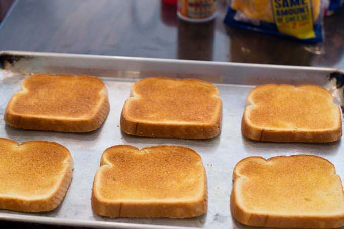Toasted bread slices on baking sheet.