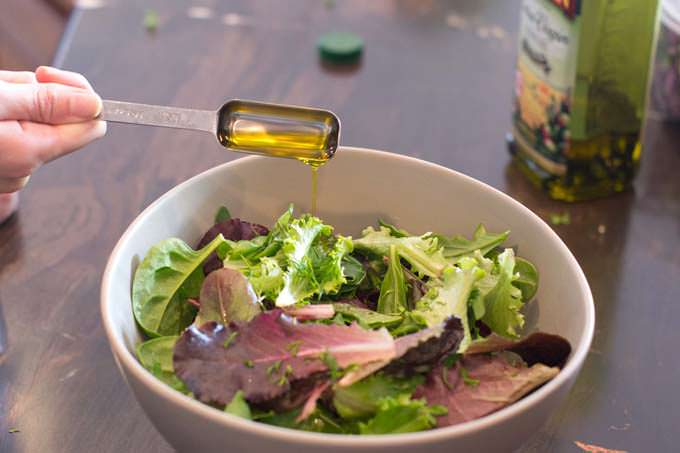 Add olive oil to the salad greens