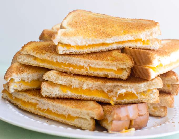 Plate of grilled cheese sandwiches, cut in half diagonally.