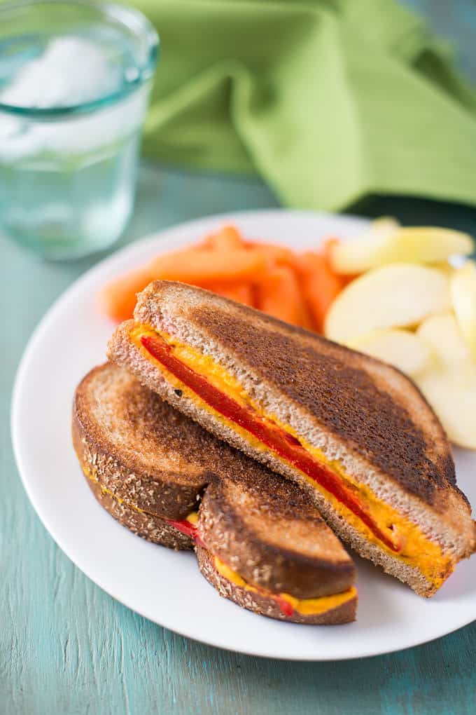 A vegan grilled cheese sandwich half is perched over another half on a plate. The cheese in the middle of the sandwich is orange with a stripe of red is facing forward. The table is a pale blue wood. There is a glass of water and a green napkin  in the background.