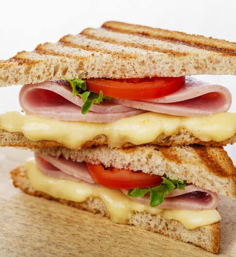 Half of a triple decker sandwich on a wooden table with a white background. The sandwich contains melted cheese, tomato, lettuce and folded ham slices.