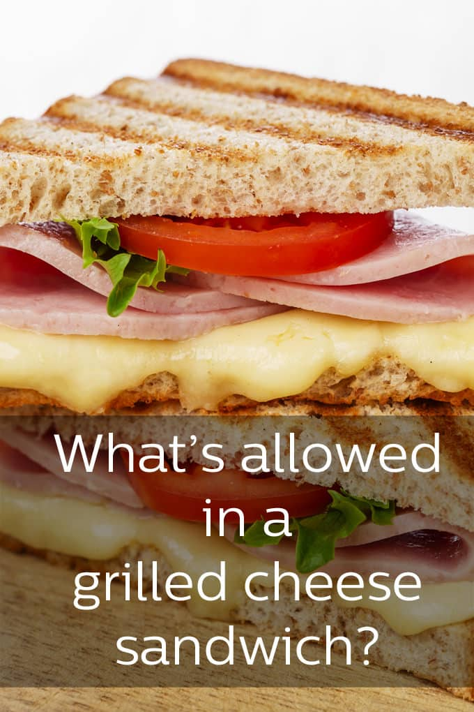 "A close up of a grilled sandwich. The top bread has even grill marks. Below it is a slice of tomato, a leaf of lettuce, two folded slices of ham and then melted cheese. The words ""What's allowed in a grilled cheese sandwich"" are overlayed onto the image."