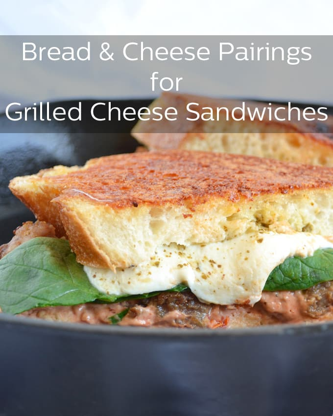 Grilled cheese sandwich with white melted cheese and green spinach in a black cast iron skillet.