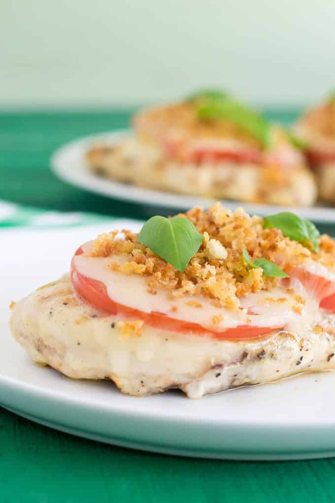 Here's a refreshing take on the classic chicken Parmesan. The chicken in marinaded in lemon and then grilled topped with tomato slices and cheese. The breadcrumb topping is killer on top.