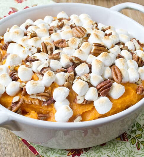 white casserole dish with mashed sweet potatoes topped with toasted marshmallows and chopped pecans; cream colored cloth with red orange flowers under dish