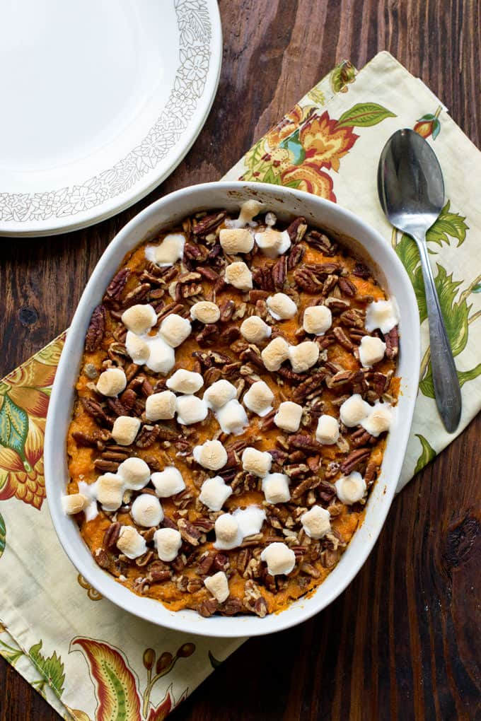 white casserole dish with mashed sweet potatoes, toasted marshmallows and chopped pecans; cream colored cloth with yellow, red, and orange flowers under dish with spoon setting on cloth; white plates with a light brown flower design around edge in corner