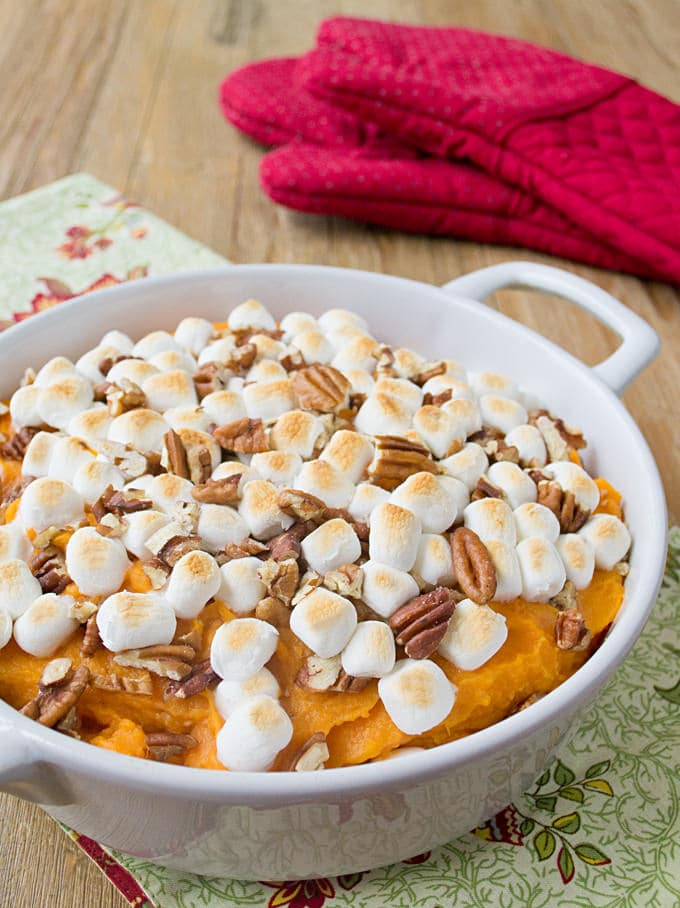 white casserole dish with mashed sweet potatoes topped with toasted marshmallows and chopped pecans; cream colored cloth with red orange flowers under dish; 2 red oven mitts in background