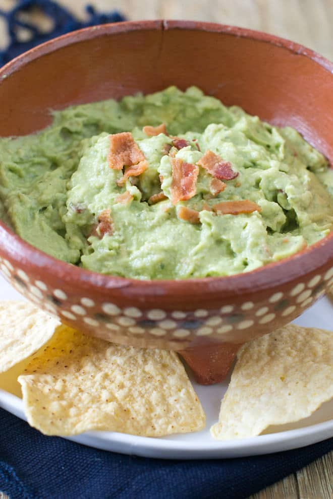 Bowl of guacamole with crumbled pieces of cooked bacon on top.