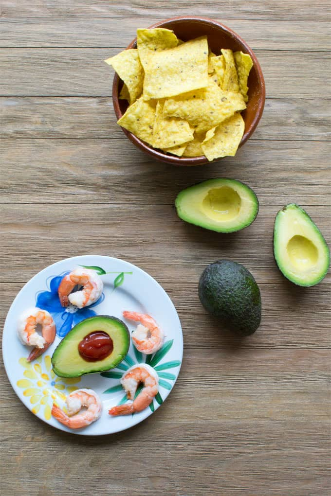 There's a divot in an avocado half for a reason. The hole is for the dip! Here we fill it with a spicy cocktail sauce and pile on some shrimp.