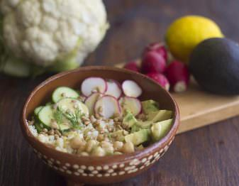 brown bowl with cauliflower rice, cucumber, radish, avocado, sunflower seeds, and dill; in background head of cauliflower, avocado, lemon, and radishes
