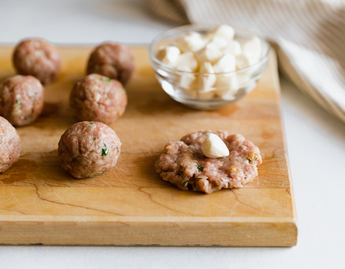 Stuffing mozzarella in meatballs on a wooden cutting board.