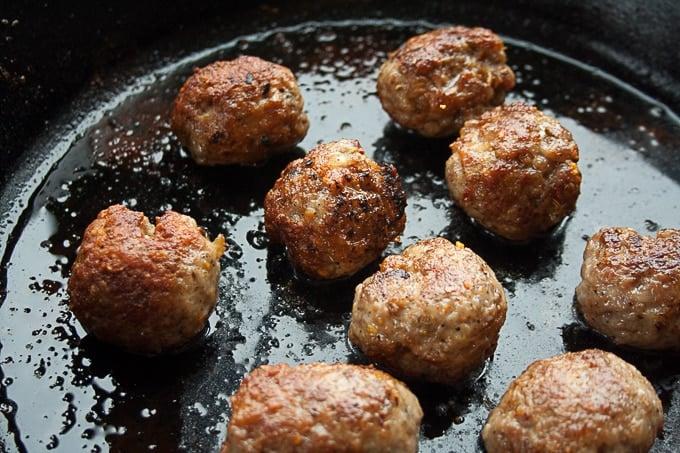 Meatballs being pan fried.