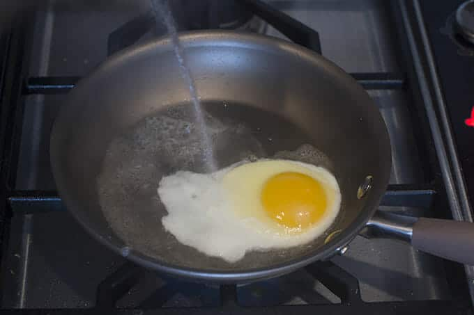 add a drizzle of hot tap water to the egg in the pan