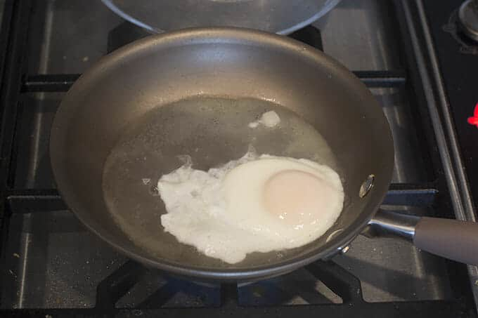 Let it cook until the steam has cooked the layer of egg whites that is over the yolk.