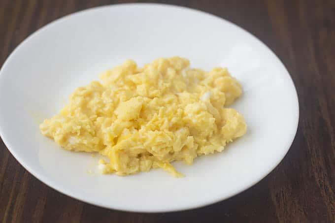 Soft scrambled eggs on a white plate.