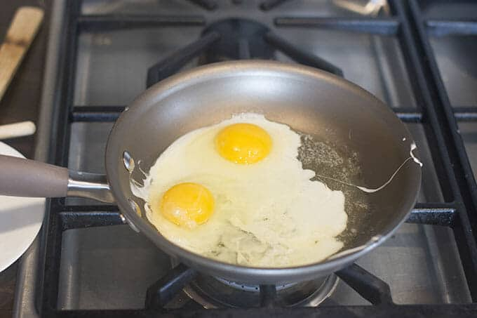 Two eggs in a pan, yolks surrounded by setting egg whites.