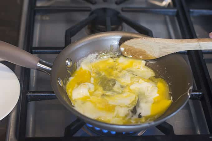 Stirring eggs while they cook in a pan.