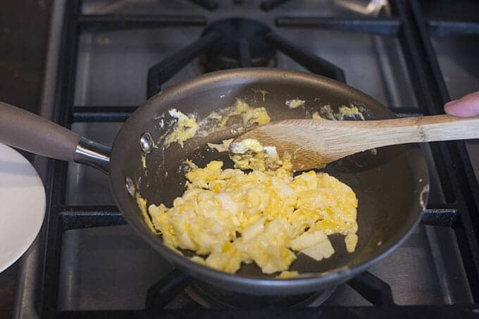 Stirring scrambled eggs until the yolks are set.