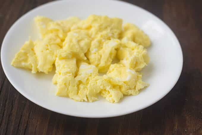 Cooked scrambled eggs on a white plate.