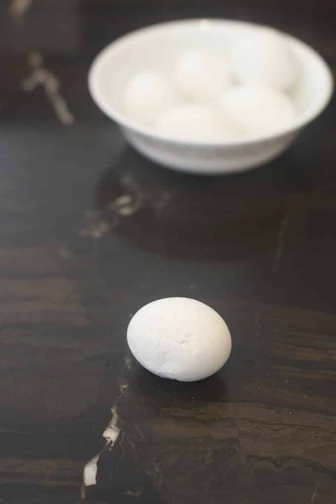 Hard cooked egg on counter that is covered in cracks.