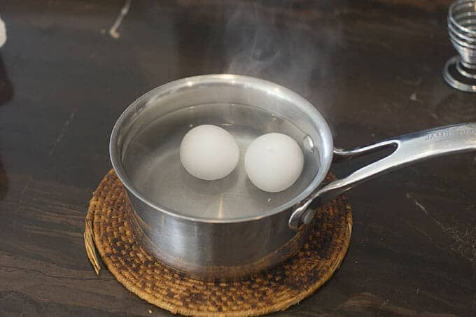 Two eggs in steaming water in a saucepan on a trivet on the counter.