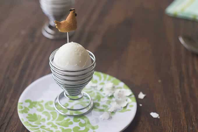 Egg in egg cup, with the top of the shell peeled away to expose the cooked egg white.