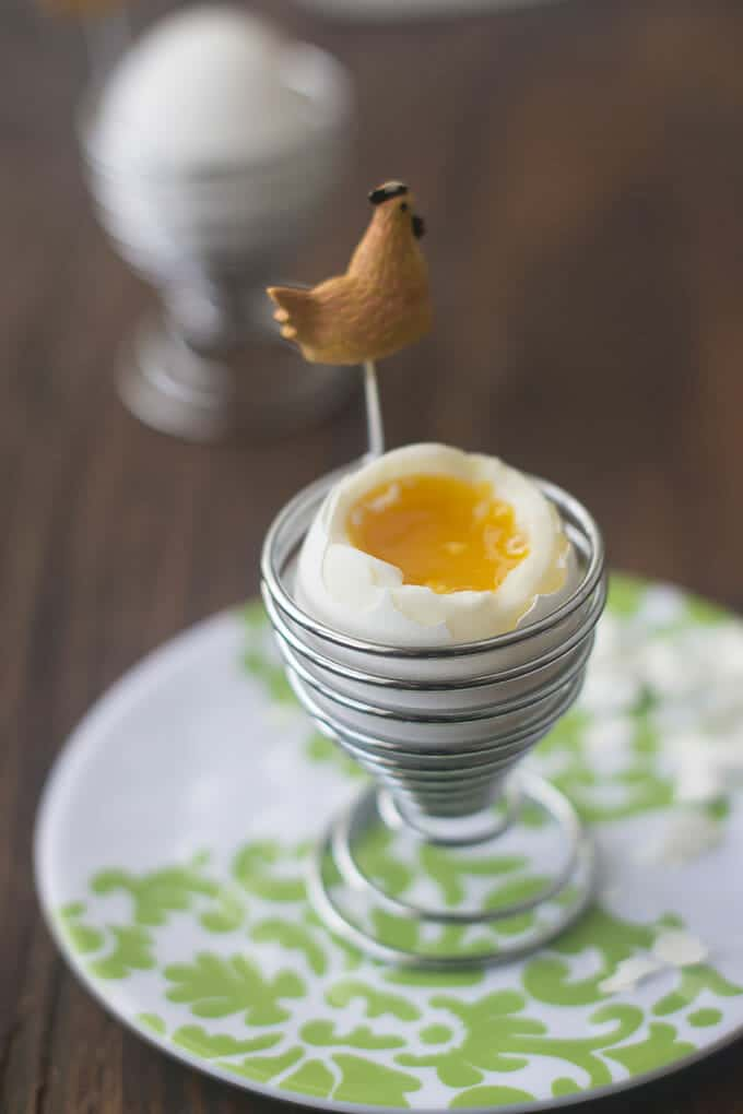 Soft boiled egg in an egg holder with a chicken figurine attached, on a green and white patterned plate.