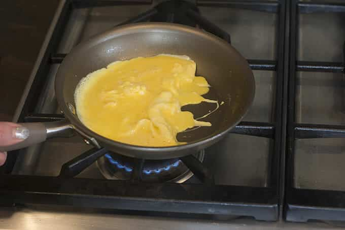 Partially cooked eggs being scraped to one side of a pan on the stove.