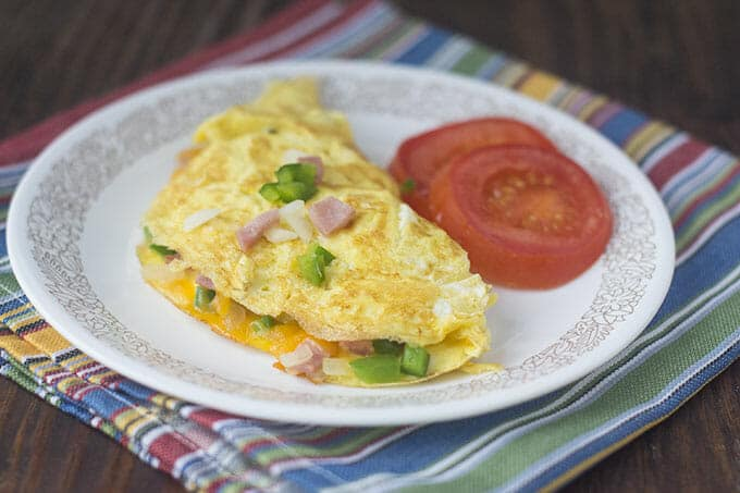 Denver omelet on a white plate with slices of tomato.