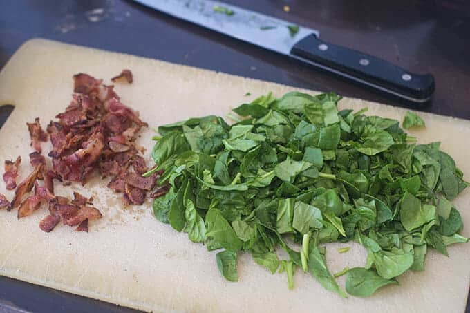 Chopped cooked bacon and chopped fresh spinach on a cutting board.