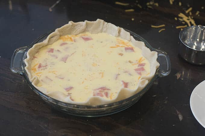 Pie dish with crust and quiche filling, ready to go in the oven.