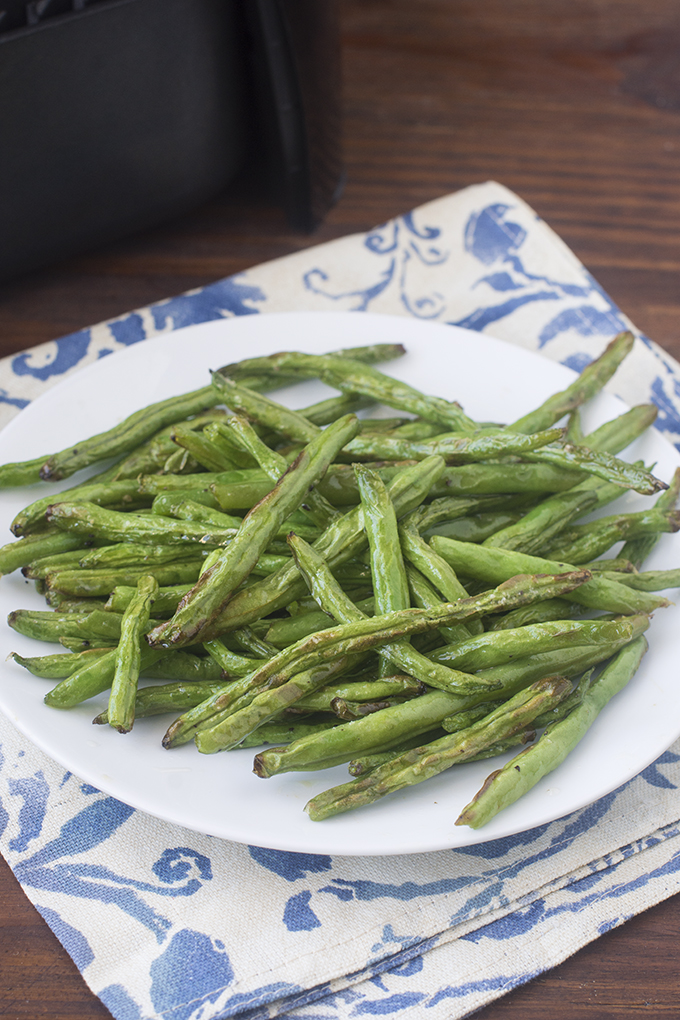The air fryer is a wonderful tool for roasting vegetables quickly. One of my favorites to cook in there is green beans. They come out softened and lightly caramelized in just 8 minutes. Sooo good!