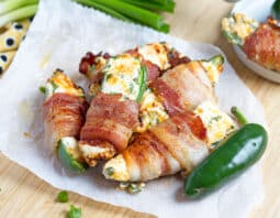 jalapenos stuffed with white filling with specks of green and orange cheddar, wrapped in bacon on parchment paper and small white plate; beige cloth with black dots in background