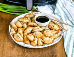 white plate full of pot stickers with condiment bowl of soy sauce and chopsticks; white cloth with blue stripes to right side with air fryer and green onion in background