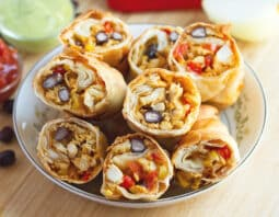 lightly browned wraps with chicken, black beans, and cheese in white bowl with light blue rim with cut red bell pepper and white onion behind it, and blue cloth; black beans scattered on light wood table; back left of image has condiments bowls with red salsa and green avocado cream;