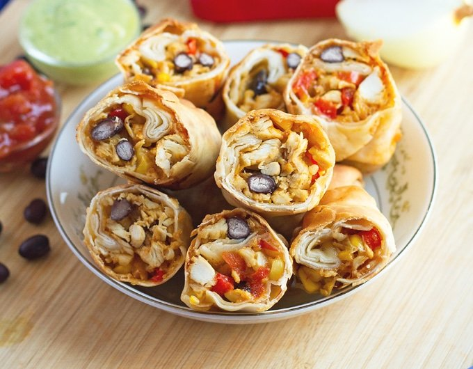 lightly browned wraps with chicken, black beans, and cheese in white bowl with light blue rim with cut red bell pepper and white onion behind it; black beans scattered on light wood table; back left of image has condiments bowls with red salsa and green avocado cream;