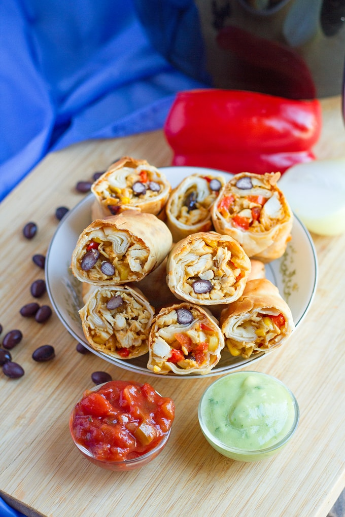 Southwest Egg Rolls made in the air fryer then served with salsa and a green salsa. Black beans scattered on brown tabletop and red bell pepper and blue cloth in background.