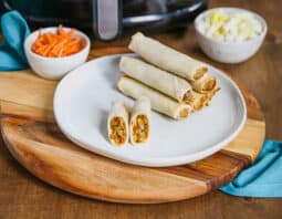 stack of 5 spring rolls on white plate on top of wooden platter; 1 spring roll cut in half on front half of plate; small bowl of shredded carrots, back left with air fryer behind it; small bowl with cabbage shreds in white bowl to back right