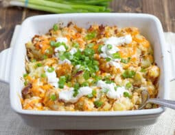 white casserole dish with potato topped with melted orange cheddar, sour cream, green onion, and bacon bits; beige cloth underneath and green onion the background; metal spoon in dish