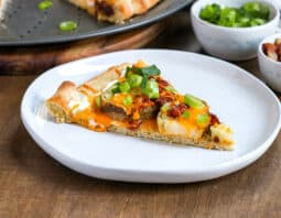 Loaded baked potato pizza in background on a metal pizza tray, one slice missing and is plated in front on white plate topped with sour cream, melted orange cheddar, green onion, and bacon bits; behind in white condiment bowls garnish of green onion and bacon bits