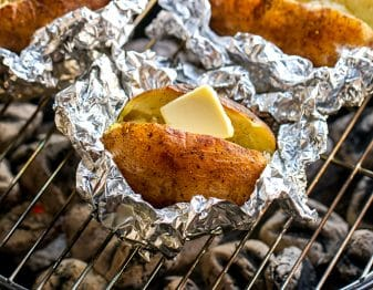 3 baked potatoes in foil; one near front of image has butter; all are on grill grate over white coals