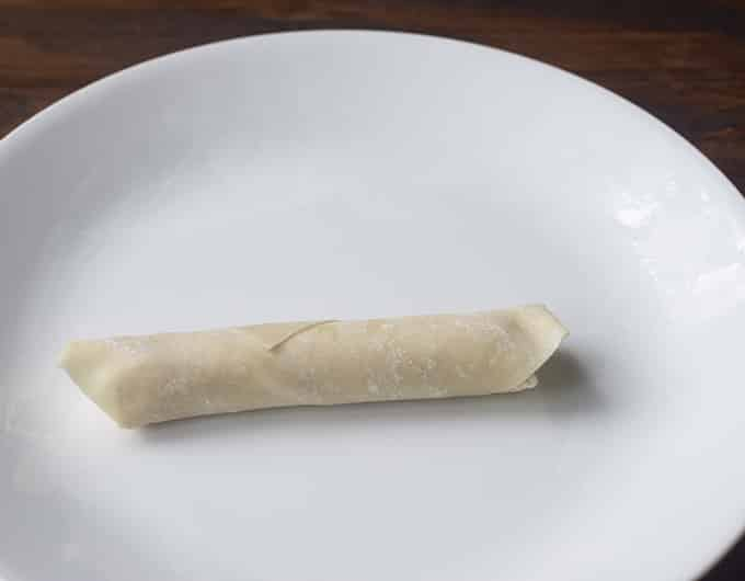 egg roll wrapper wrapped around cheese stick on white plate