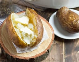 baked potato with butter on foil on wooden log round with beige and black plaid cloth underneath; another baked potato uncut on small white plate; salt and pepper and white slow cooker in background